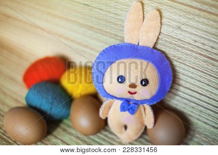 Easter Bunny Toy With Color And Pure Brown Eggs In The Chaff Background. Red, Yellow And Green Eggs.