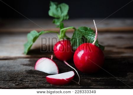Horizontal Dark Low Key Image Of A Few Red Radishes With Green Leaves Lying On A Rustic Wood Backgro