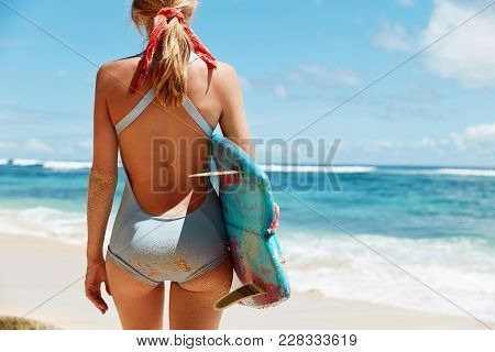 Horizontal Shot Of Slender Female In Blue Bathing Suit, Stands Back To Camera, Has Fit Butt Holds Su