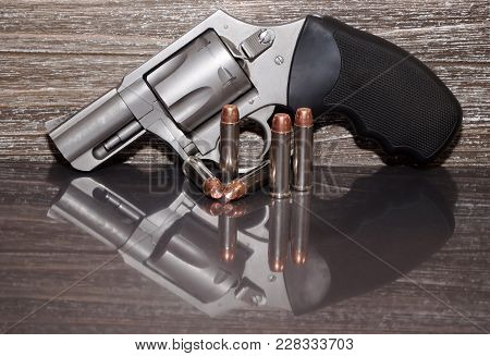 A Stainless Steel 357 Magnum Revolver With Five Bullets In Front Of It With A Wooden Background And