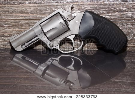 A Stainless Steel 44 Special Magnum Revolver On A Reflective Surface With A Wooden Background