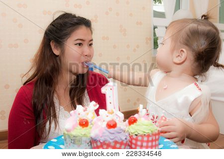 Happy Pregnant Mother And Her Baby Daughter Having Fun And Enjoy Eating At Birthday Party With Birth