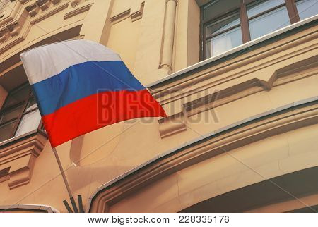 The national flag of the Russian Federation on the wall of the building. Toned