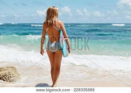 Full Length Portrait Of Slim Female With Light Hair, Wears Blue Swimsuit, Stands Against Ocean Beaut