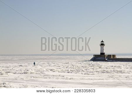 Person Walkingon Frozen Lake Superior Along Pier With Lighthouse In Duluth, Minnesota