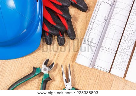 Rolls Of Diagrams And Electrical Construction Drawings, Protective Blue Helmet With Gloves And Metal