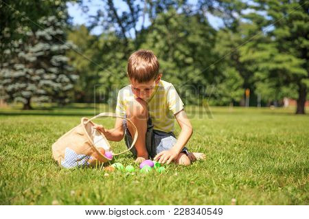 Boy With A Basket Of Easter Eggs Outdoors. Happy Boy Pick Up Colorful Eggs. The Concept Of Easter Eg