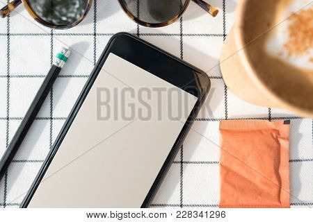 Top View Of Mobile Phone With Blank Screen With Coffee Cup,sunglasses,pencil On White Table Cloth.in