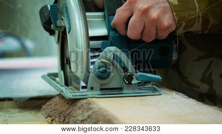 Cutting Wooden Floor By Electric Saw. The Carpenter Saws A Log Or Board