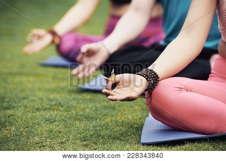 Butterfly On Hand Of Meditating Young Woman