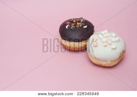 Doughnuts With Chocolate And White Icing On Pastel Pink Background. Sweet Dessert Donuts With Copy P