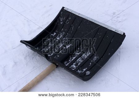 Plastic Shovel For Shoveling Snow With A Wooden Handle And A Black Handle Isolate