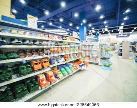 Blurred Of Kids Toy Store Background With Bokhe. Shelves With Cars And Aisle Of Kids Toy Shop Interi