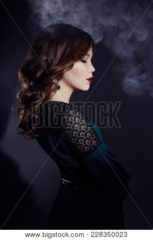 Art Portrait Of An Asian Young Brunette Woman In A Smoke On A Black Background. Mysterious Mystical
