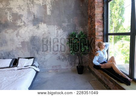 Attractive Young Woman Poses With Smile And Sits On Window Sill