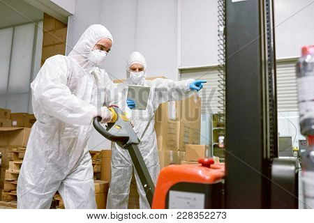 Concentrated Young Worker Wearing Coverall And Safety Mask Using Hand Pallet Truck While Working In