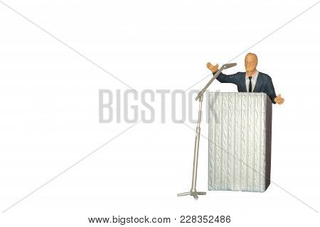 Miniature People Of A Politician Speaking With Microphone Isolate On White And Clipping Path