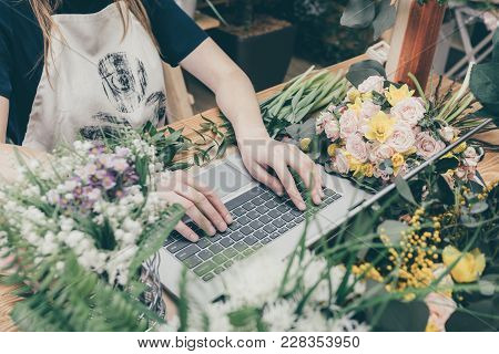 Faceless View Of Saleswoman In Apron Browsing Laptop Sitting At Table With Flowers In Market.