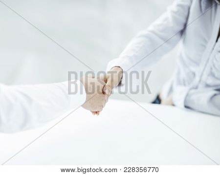 Handshake Manager And Client On A Background Of Bright Office .the Photo Has A Empty Space For Your