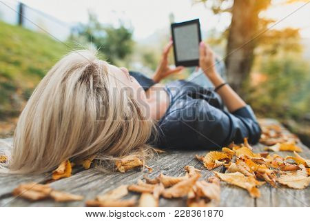 Blonde Girl Reads A Book From Her Ebooks Readers.