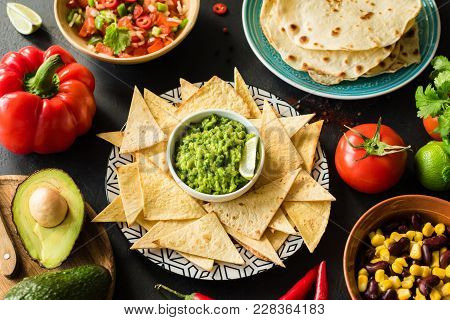 Mexican Food Guacamole Nachos Tortilla Chips Salsa And Beans On Dark Table. Food Plate, Mexican Cuis