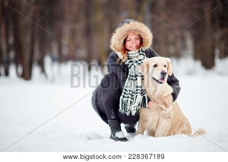 Photo Of Girl In Black Jacket Squatting Next To Dog In Winter Park During Day