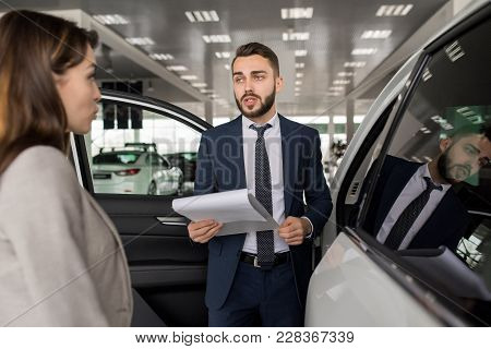 Portrait Of Handsome Car Salesman Showing Luxury Cars To Young Woman In Dealership Showroom