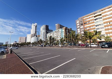 Empty Parking Bays Against  Beachfront City Skyline