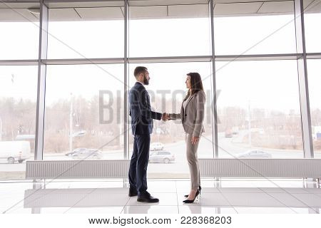 Side View Full Length Portrait Of Two Business Partners Shaking Hands Standing Against Big Window In