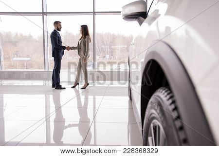 Wide Angle Portrait Of Car Salesman Shaking Hands With Woman Buying New Car In Dealership Showroom,