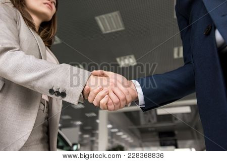 Low Angle Close Up Of Businessman Shaking Hands With Woman After Mutually Beneficial Deal, Copy Spac