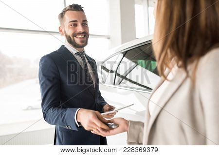 Portrait of handsome car salesman giving car keys to young woman standing next to white shiny luxury car in dealership showroom poster