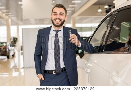 Portrait Of Handsome Car Salesman A Holding Car Keys And Smiling Cheerfully At Camera Posing In Luxu