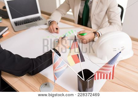 Portrait Of Two Unrecognizable Business People Drafting Plans Sitting At Desk In International Agenc