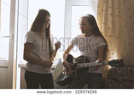 Two Female Teens Playing Musical Instruments In Front The Window At Home, Youth Hobby And Leisure Co