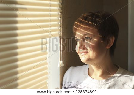 Middle-aged Woman Standing In Front Of A Window In Daylight, Dreaming And Smiling, A Shade Of Blinds