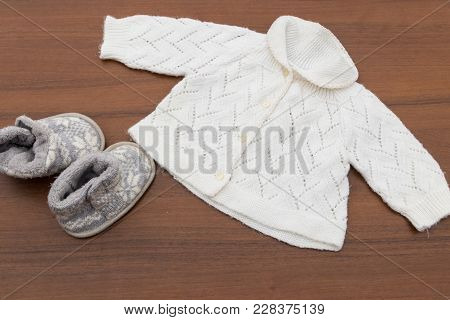 Baby Clothes And Booties On Wooden Background