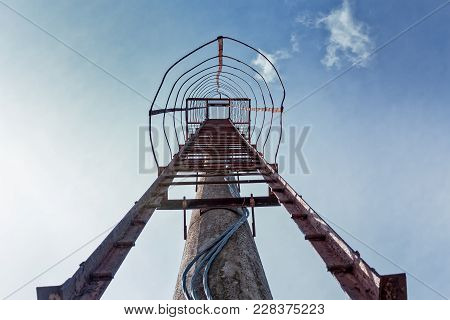 The Iron Ladder Leads To The Concrete Light Tower At A Sports Stadium In Tallinn, Estonia. These Old