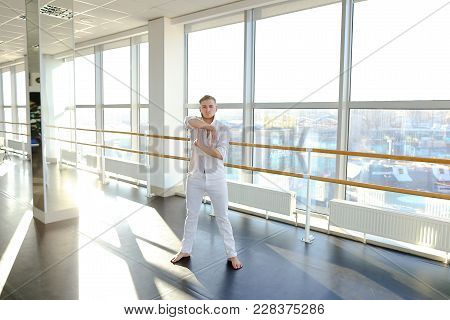 Street Style Dancer Doing Hand Vigorous Actions Near Windows. Blonde Guy Wears White Suit. Concept O