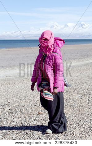 Ngari, Tibet - May 7: Tibetan Girl Pilgrim Walking On The Road Across Holy Manasarovar Lake On May 7