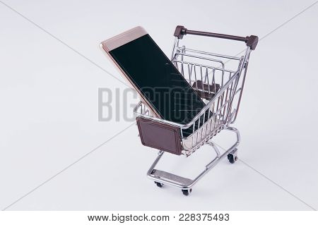 A Shopping Cart With Smartphone Inside, Indicating Mobile Commerce And E-commerce