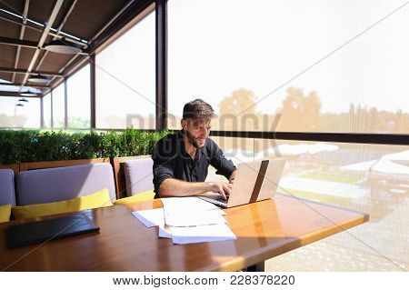 Tired Quantity Surveyor Working At Cafe Table With Diagram And Statistic Documents. Persistent Man D