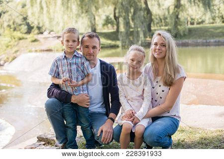 Mom And Dad Playing With Their Handsome Son And Daughter - Family And Children Outdoors In The Park