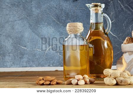 Conceptual Composition Of Transparent Glass Oil Jars With Different Kinds Of Nuts Such As Walnut, Pe