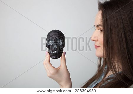 Young Girl Holding A Small, Black Skull At Eye Level And Looking Straight At Him, On A White Backgro