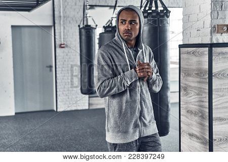 Tired After Workout. Tired Young African Man In Sport Clothing Looking Away While Standing In The Gy