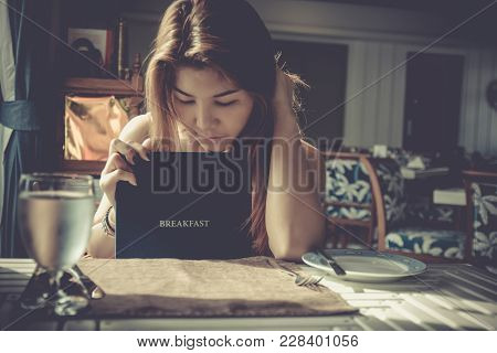 Beautiful Woman Looking Restaurant Menu Deciding What To Order.  Young Girl Waiting To Order, Open M