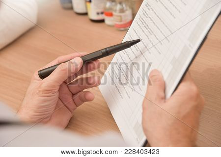 Close Up On Hands. Asian Senior Male Doctor Is Holding A Clipboard, Prescription, Paper Work, Patien