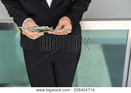 Close Up Female Hands Counting Money. Woman In Black Suit Recounts Usd Dollar Notes. Business Girl W
