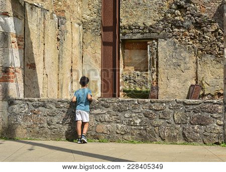 The Boy Looks At The Ruined Building Or House During World War 2 In Oradour Sur Glane France